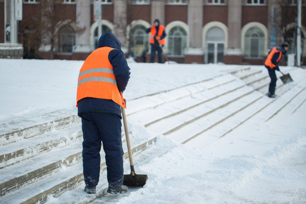 Crew clearing snow on commercial building steps